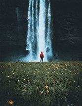 person in a rain jacket standing in front of a waterfall
