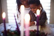 mother and son reading a Bible near an Advent wreath