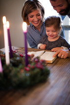 a family reading a Bible in front of an Advent wreath