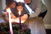 family reading a Bible in front of an Advent wreath