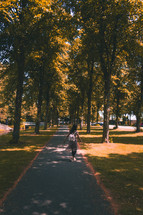 a woman walking on a paved path in a park
