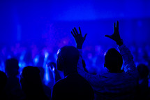 audience under blue light with hands raised