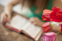 Woman reading the Bible on a table with tulips.