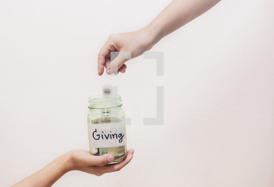 putting money in a giving jar