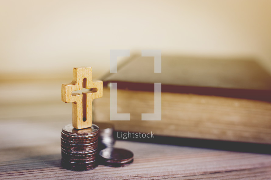 Bible, stack of coins, and cross