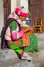 Woman in traditional Chinese minority tribe clothes sewing whilst sitting on stairs