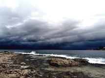 dramatic rocky shore with a storm approaching on the horizon