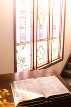 open Bible and a stained glass window