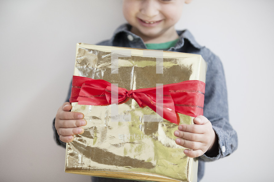 A child holding a wrapped Christmas gift.