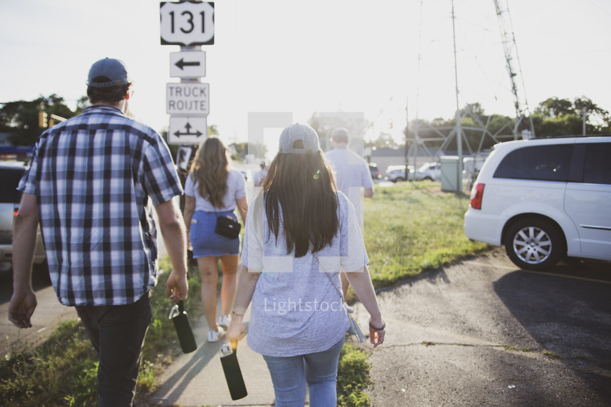 group of people walking down a sidewalk
