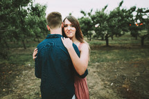 a couple hugging in an orchard