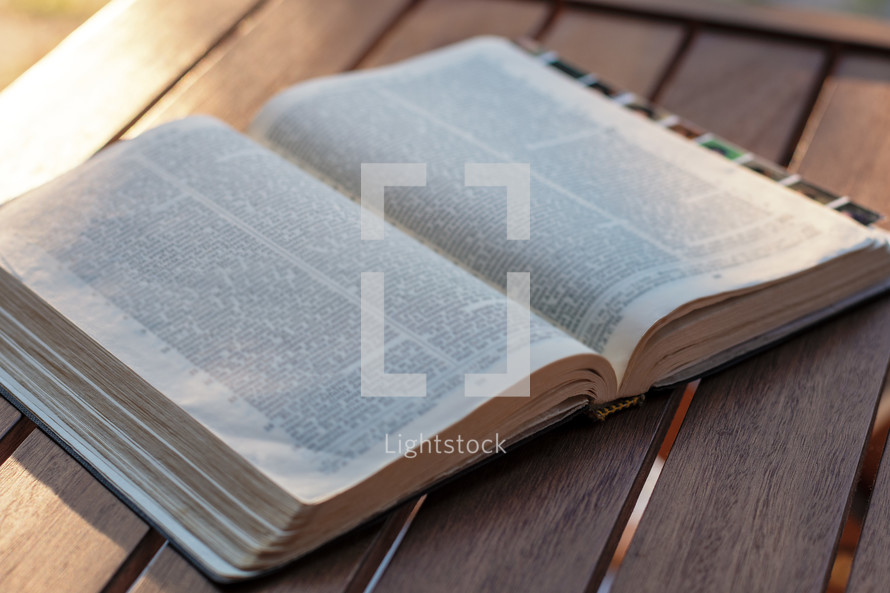 open Bible on a wood table outdoors
