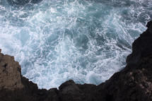 ocean water at the bottom of a cliff