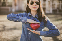 A young woman wearing sunglasses and holding a red heart