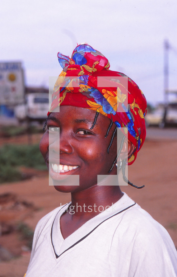 a smiling girl wearing a scarf on her head