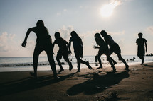 silhouettes of a family running on a beach