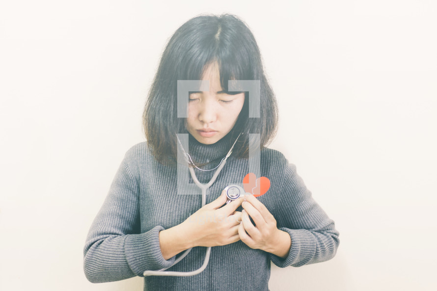 a woman holding a stethoscope and a broken paper heart