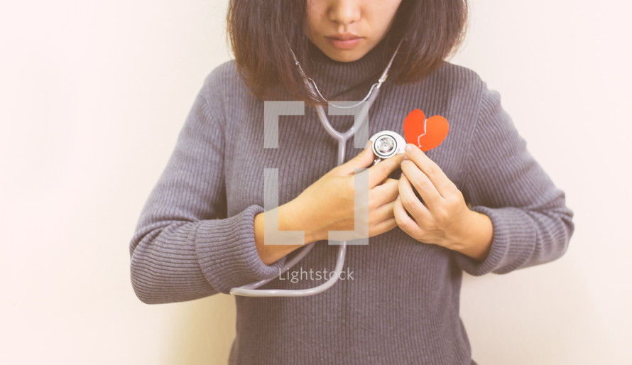 a woman holding a stethoscope and a broken red paper heart