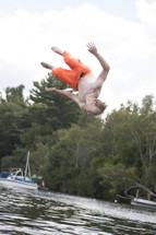 Teenage boy doing a flip over open water and upside down
