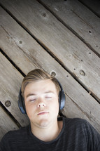 Teenager listening to music and lying down on wooden background
