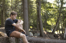 Teenager sitting on log in woods and praying with head down