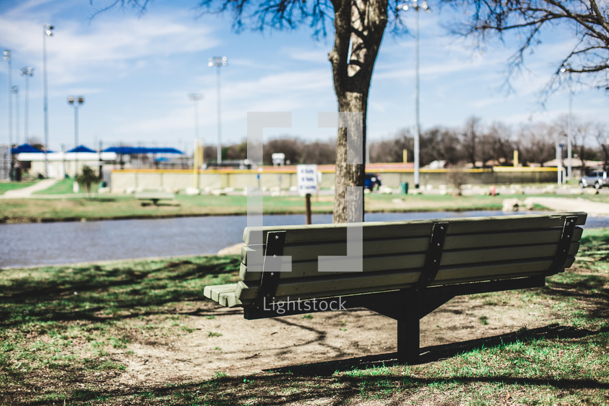 park bench with a view of a ballpark