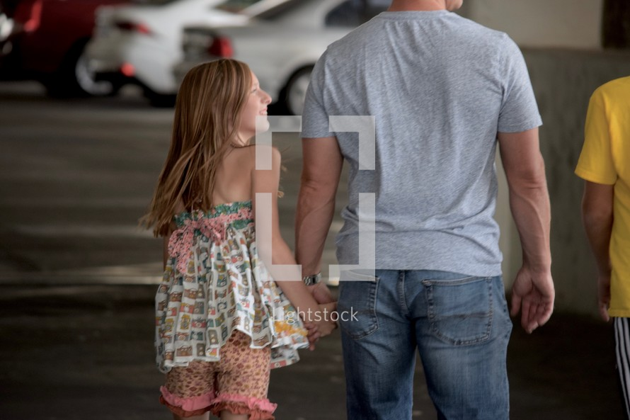 father walking holding hands with his kids in a parking garage