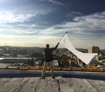 A man on a rooftop waving a white flag.
