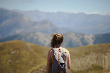 a woman backpacking through a mountain landscape