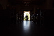 silhouette of a bride and groom in the doorway of a church