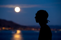 silhouette of a teen boy under moonlight