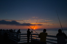 silhouettes of people fishing on a pier at sunset
