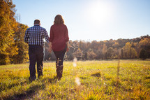 Couple walking through a field with fall foliage.