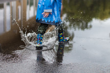 a child in rain boots splashing in puddles