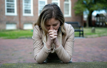 a woman praying on the ground