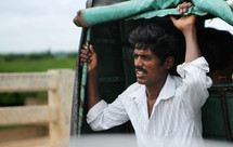 man in India riding on the back of a truck