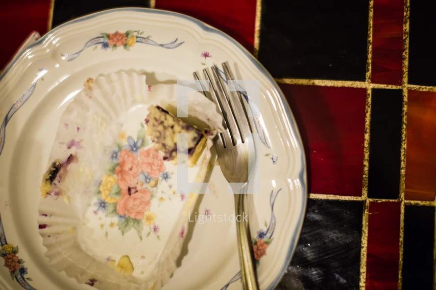 Cake crumbs and fork on a plate.