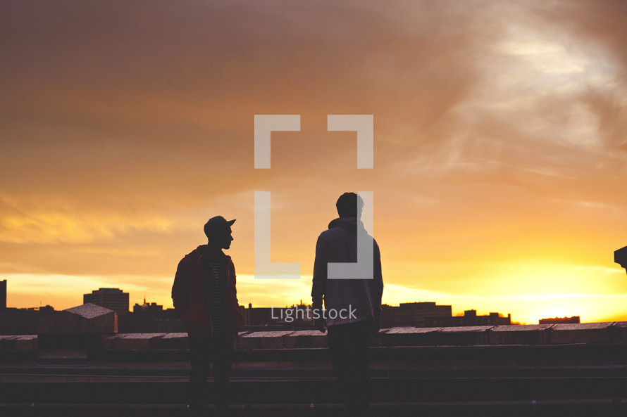 Two young men on city rooftop at sunset.