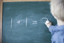 A child doing math on a chalk board.