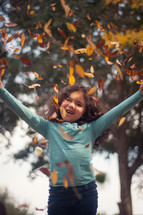 girl throwing up fall leaves