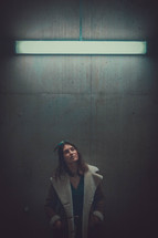 a woman standing under a florescent lights