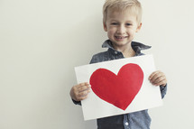 toddler boy holding a painting of a heart