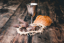 communion elements, crown of thorns, and three nails