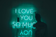 a man standing near a neon sign that reads I love you so much