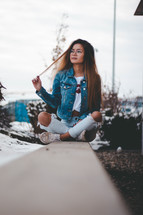 a teen girl sitting alone outdoors