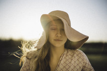 a young woman with closed eyes in a sun hat