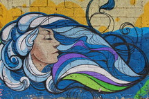 Graffiti painting of a woman with flowing wavy blue hair on a brick wall background