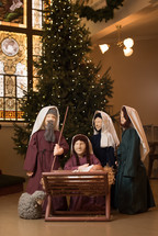 Christmas tree and figurines of Mary, Joseph, and Baby Jesus in a church