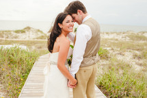 a bride and groom holding hands on a beach boardwalk