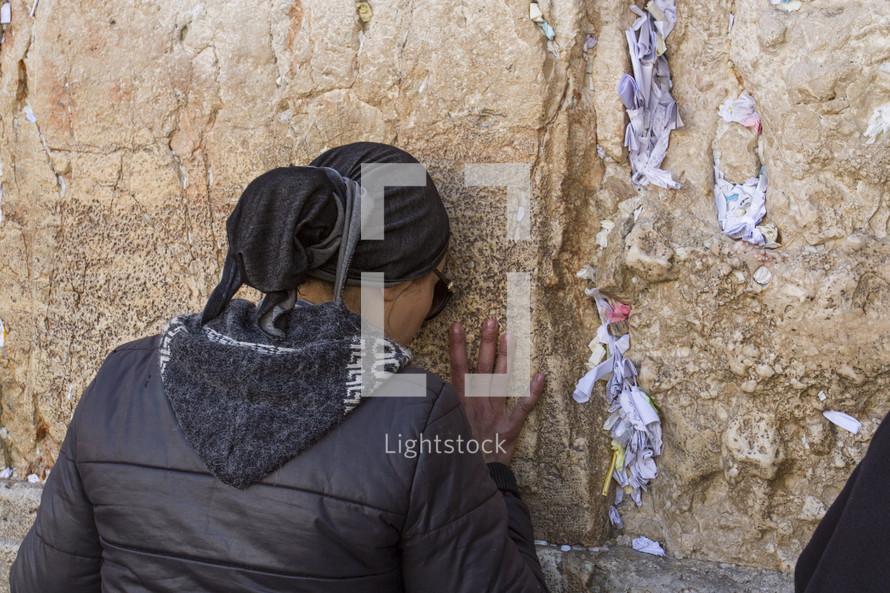 a woman praying against a wall